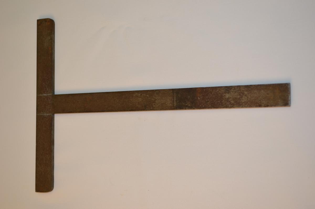 Vinkel i stål forma som ein T. Denne låg i ei verktøykasse frå ein boktrykkar.