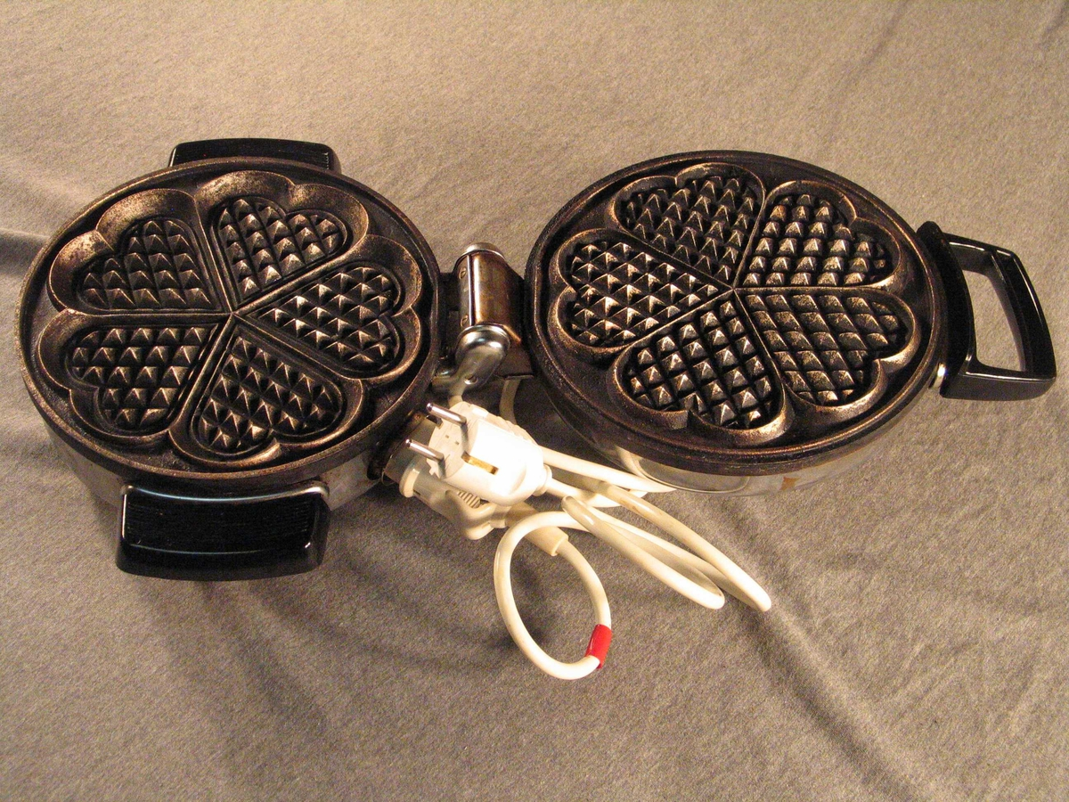 Gjenstandsnummeret består av jern med laus ledning. Jernet har to kompakte ledda deler og står på kraftige føter. Midt på toppen er det gripeknott.