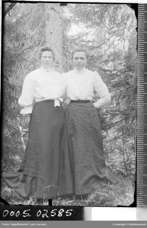 Portrett av to kvinner ute i skogen..