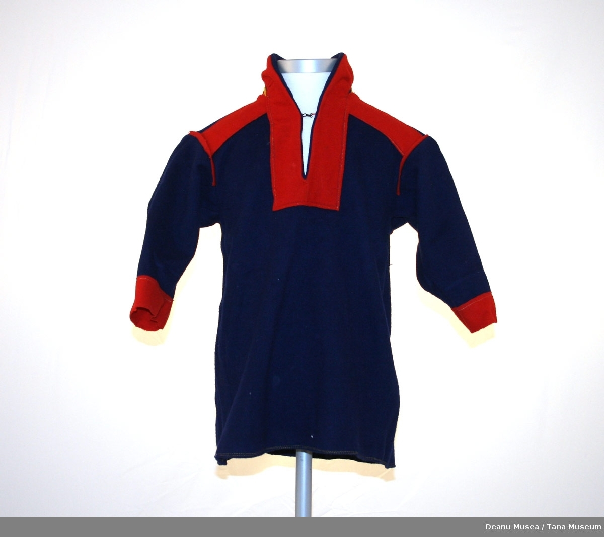 Mørkeblå barnekofte (4 år). Rød ermer/hals. Rød og gul polmak mønster på rygg og skulder.