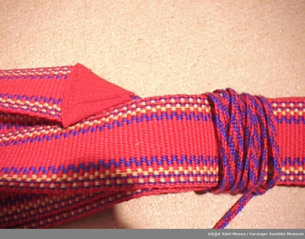 Et par grindvevde skallebånd med rød som hovedfarge og langsgående striper i blått og gult. En kort bred flette i den ene enden til å feste båndet i skotøyet og en lang tynn flette med dusk i den andre, til å surre rundt leggen.