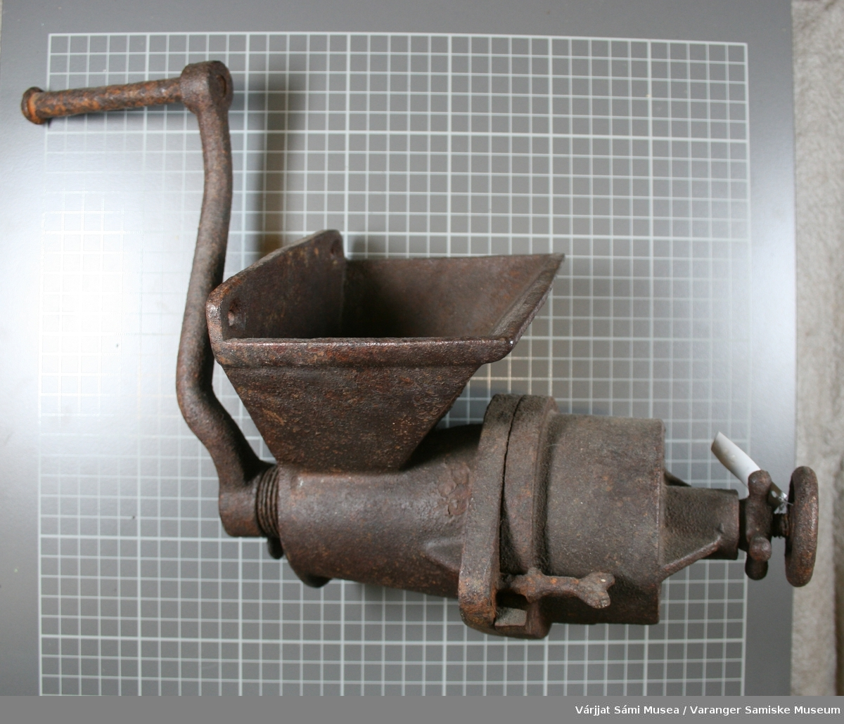 Kjøttkvern av metall med en rull.  På kverna er det slått inn følgende: 1937  KyM