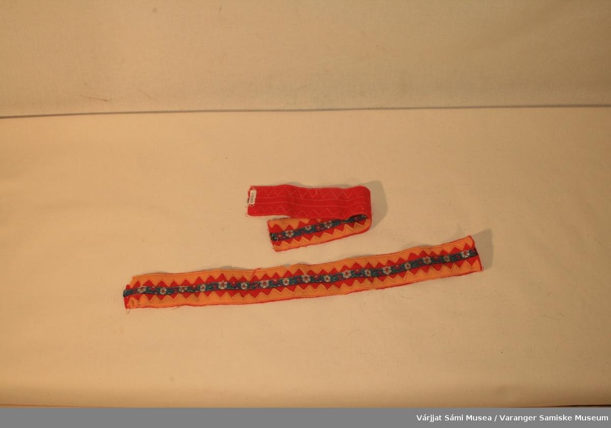 To pyntebånd. Bunnen er  rødt klede. Gule sikksakk mønster i kantene og blå mønstret bånd i midten. Pyntebåndene kan være brukt som pynt til skaller. En kan se at disse er klipt løs i fra noe.
