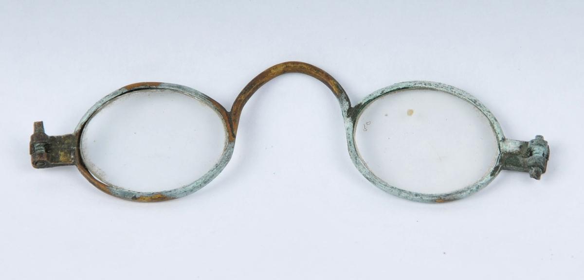 Briller i messing med glas. Delvis maskinelt utført.  Nasebøyla er lodda til innfatninga. Innfatninga er skruva saman på yttersida av glasa og her er det også feste for brillestenger.