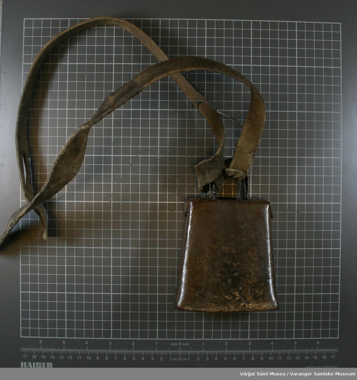 Bjelle av metall, den er klinket fast på hver side med to nagler, hank på toppen med skinnreim gjennom.