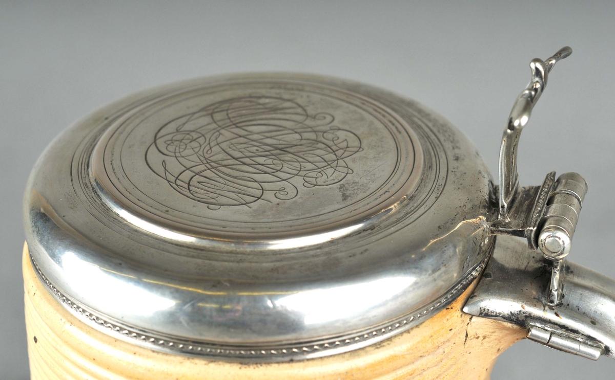 Brunt keramikkrus med sylvlok. 10 smale ribbar i keramikken nede og 10 oppe i kanten.  I øvre kant er det ei hank av keramikk. I denne er det festa eit massivt sylvlok. Hevearm til å vippe upp loket med. Oppå loket ei plan flate som har gravering av eit speglmonogram i tre eller fire bokstavar. Monogrammet er vanskeleg å tyde, men inneheld bokstaven M.