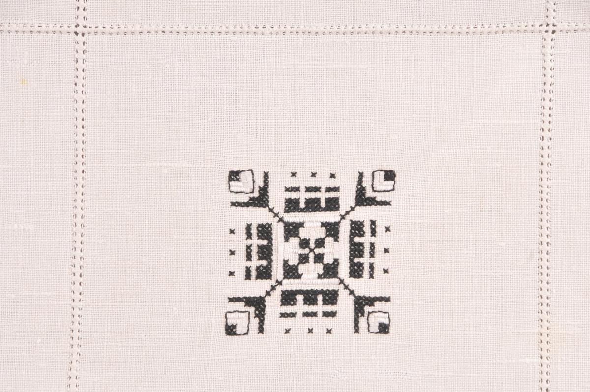 Duk i ubleika lin (14x15 trådar pr cm) der rader med samantrekkssaum utgjer rutemønster (6x6 ruter). Inne i dei rutene som dannar diagonalane på duken er det brodera motiv med korssting og rett plattsaum i kvitt og svart brodergarn. Dobbellagt fald sydd ned med faldesting langs alle sider.