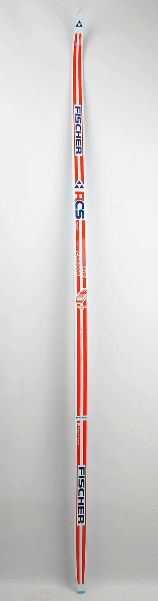 Langrennski laga av glasfiber, med såle av plast. Kvit overflate, raude dekorstriper, raud og blå skrift. Skia er ekstra lette pga måten kjernen er støypt på (lufthol).