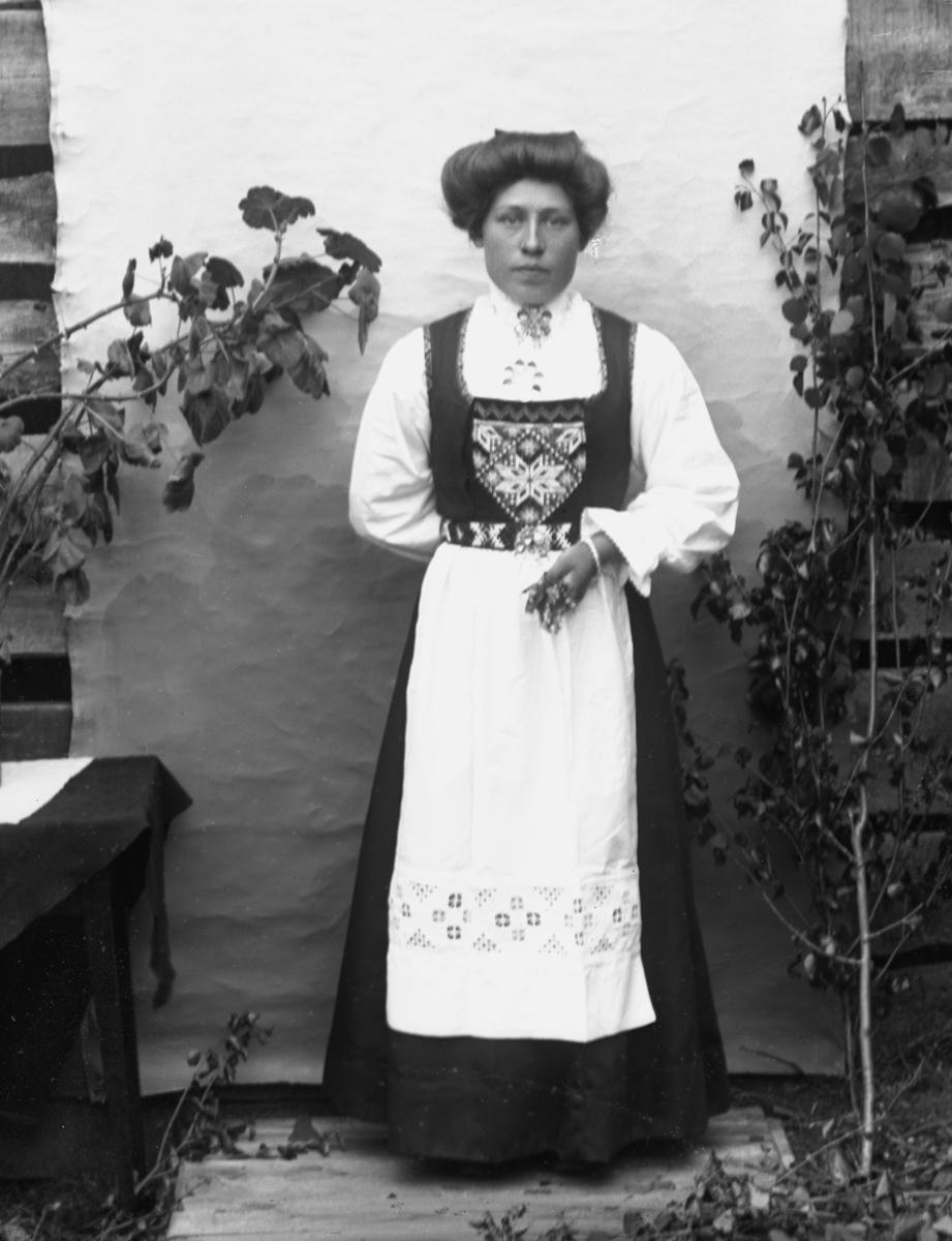 """Kvinne kledd i bunad/""""nasjonaldrakt"""", stående foran lerret på husvegg"""