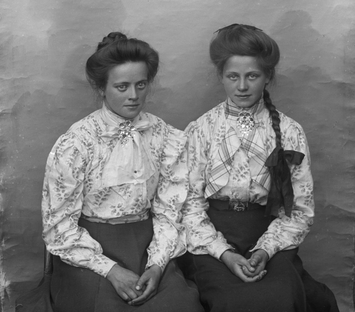 To unge jenter kledd i mønstrete lyse skjorter med søljer, den ene jenta med lang synlig flette. Lerretbakgrunn