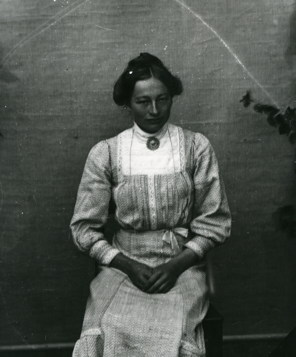 Kvinne kledd i lys og mønstrete kjole, sittende foran lerret