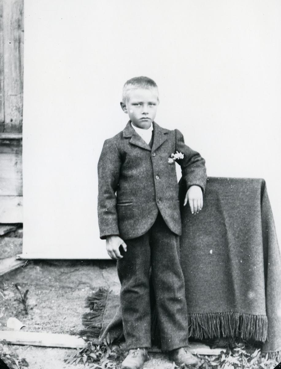 Dresskledd gutt ved tildekket stol, lerret festet på husvegg