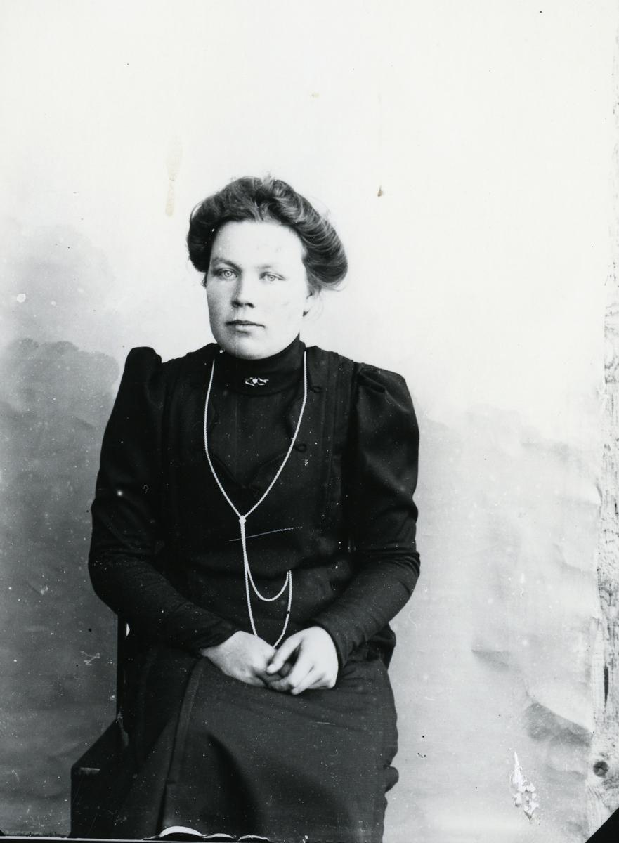 Kvinne i mørk kjole, sittende foran lerret