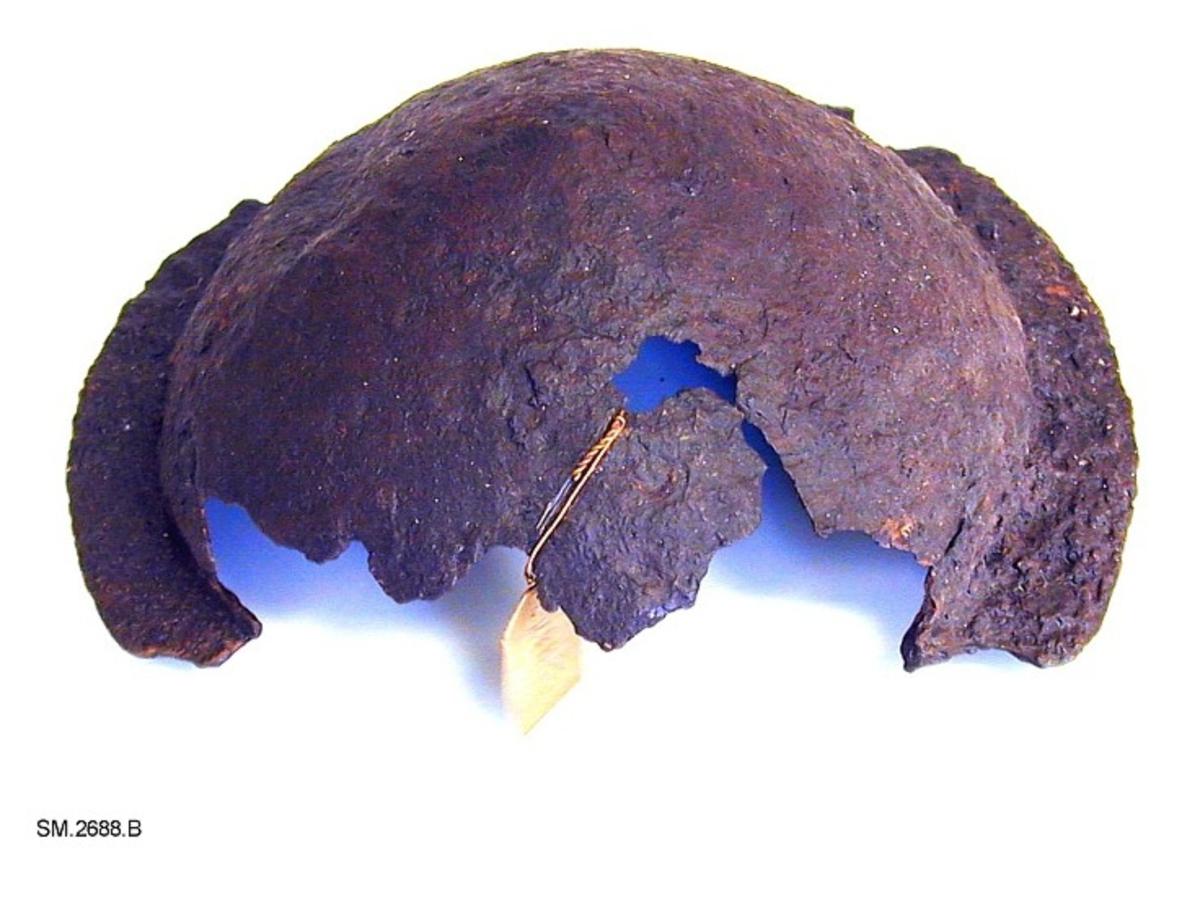 Fra protokollen: Skjoldbule av jern, som Rygh 562, men ikke fullt så lav, nærmere kjegleformet. Bulen er en del forrustet og noe defekt, særlig på den ene siden.  SM.2687-2688: Funnet samlet på en åker i en kiste av tynne steinheller. I nærheten flere gravhauger. Her sto også en runestein, som i 1864 ble sendt inn til Universitetets Oldsaksamling, C.3497, se Norges Innskrifter med de yngre runer, bind II, s. 214 ff. Runeinnskriften er av kristen karakter, men synes å ha stått på et hedensk gravminne, Glomshaugen. Den dateres til midten av 12. årh., mens vårt funn helst hører hjemme i midten av 10. årh., men kan også være senere, gå ned i 11. årh.