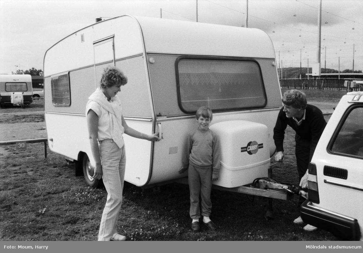 """Campare vid Åby camping i Mölndal, år 1984. """"Vi är ute med husvagn för första gången, berättar Tommy, Monica och Jimmy Olofsson från Hälsingborg, så något att jämföra med har vi inte, men det känns bra här på Åby. Vi har tänkt stanna några dagar och kommer att besöka Liseberg. Men även Mölndalsbro, simhallen och Gunnebo slott är tänkbara komplement till det stora nöjesäventyret.""""  För mer information om bilden se under tilläggsinformation."""