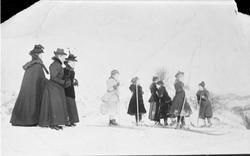 Tre pent kledte kvinner ser på seks jenter som går på ski.