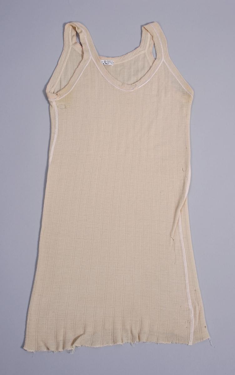 Plagget er maskinstrikket med søm i sidene. Påsydd kantebånd rundt erm- og halsrigning. Båndene fungere som skulderstropper.