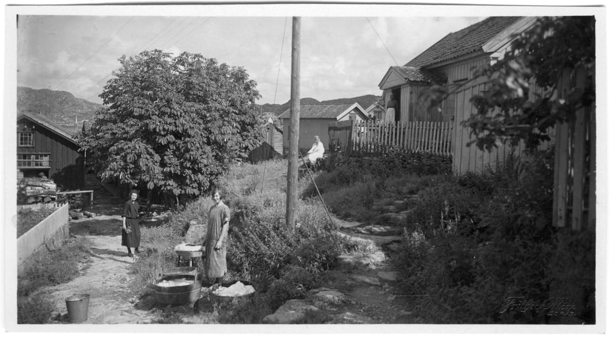 'Nedgång till ''Söderns'' tilläggsplats. Till vänster Hermanssons gård, t.h Albertina Hellmans. 2 kvinnor i förgrunden, den ena vid tvättkar och den andra med blombukett i handen. På farstutrappan till huset till höger står 1 kvinna och 1 person sitter på trappa nedanför huset. Kläder. Klädsel. ::  :: Serie fotonr 1888-1963.'