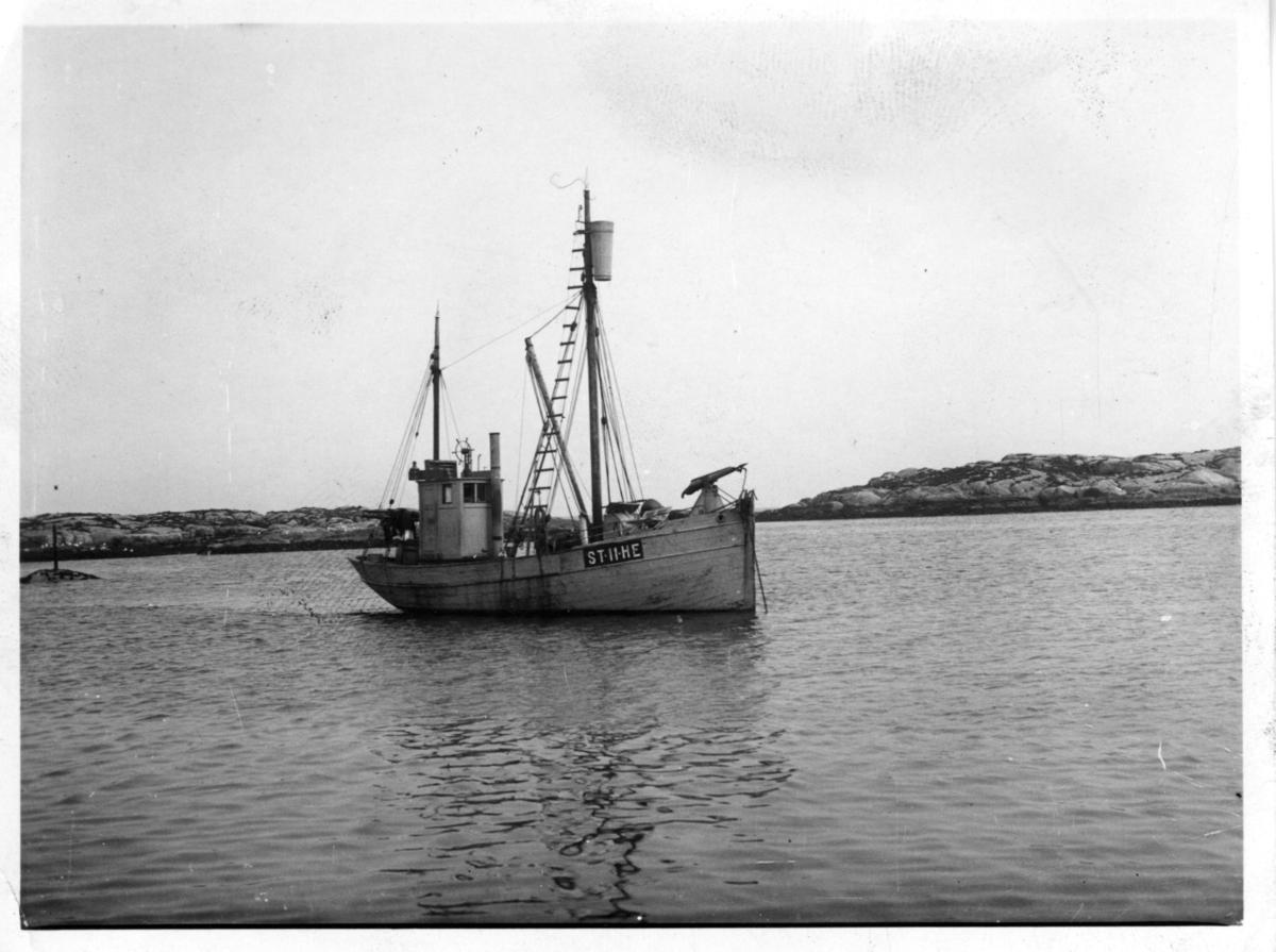 'Båten ''ST-11-HE'' på öppet vatten, i bakgrunden är klippor synliga. ::  :: Ingår i serie med fotonr. 3679-3693 se även 3694-3719.'