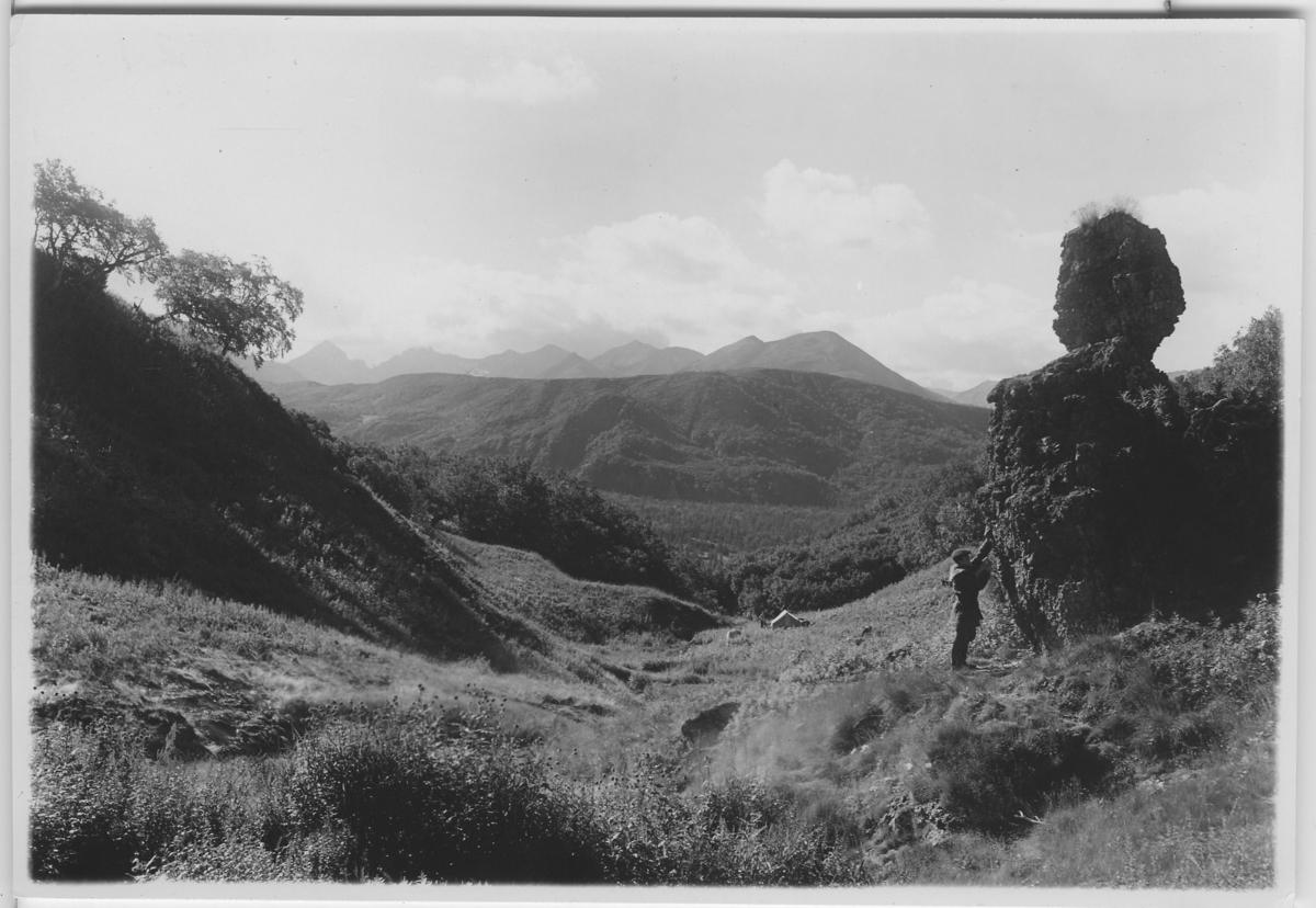 'Vy över dal, i förgrunden het källa och avgudabild av calcedon (den syns ej) En man samt ett tält är synligt. ::  :: Serie fotonr 4916-4930. :: Kartskiss fotonr. 4916:1 visar motivens läge.'