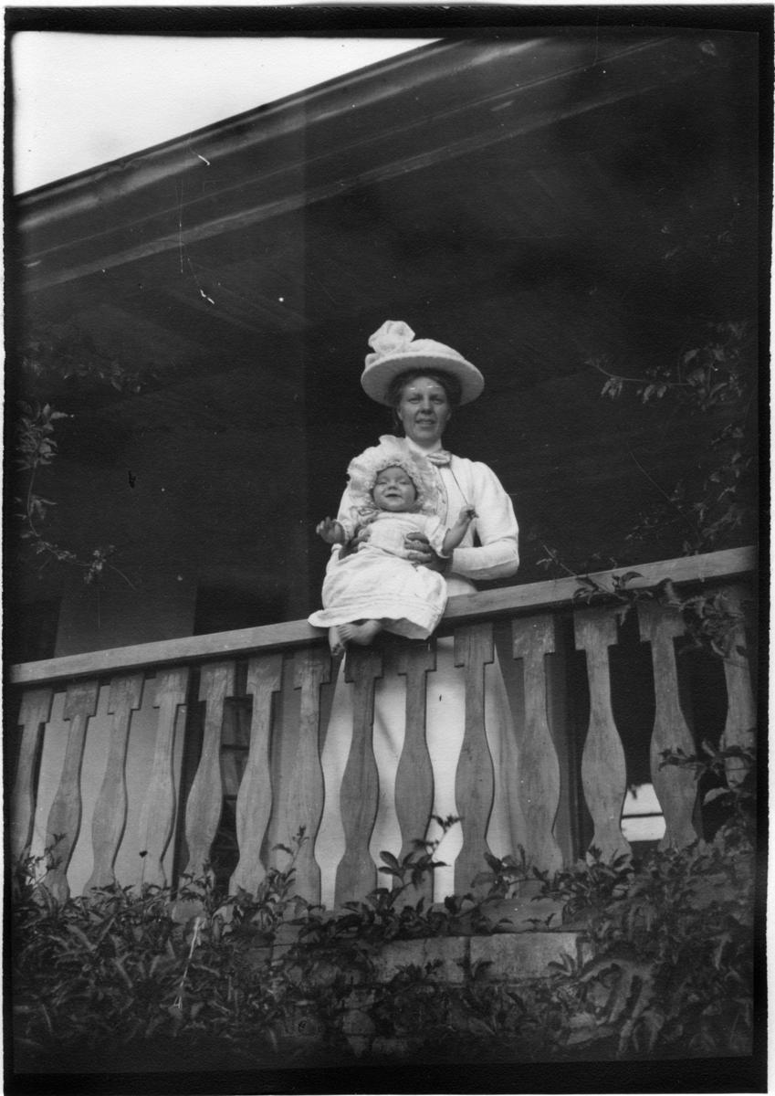 'Diverse fotografier från bl.a. dåvarande Nordrhodesia, nu Zambia, tagna av Konsul Magnus Leijer. ::  :: En kvinna ståendes på en veranda vid räcket, på räcket håller hon en sittande, skrattande bebis.'