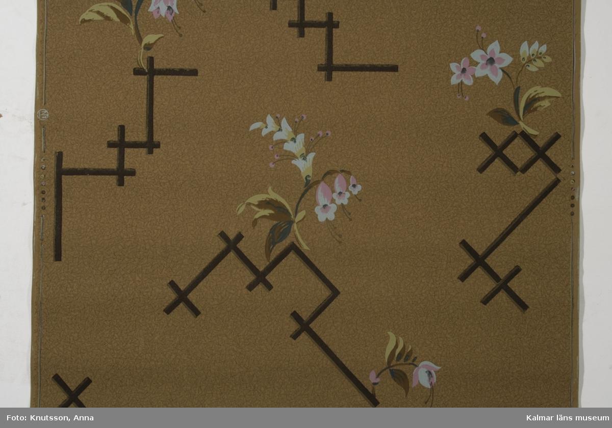 KLM 39764:11. Tapet av papper. Brunmelerad bakgrundsfärg, klockliknande blommor i ljusblått och rosa. Blad i brunt, grönt och beige. Svarta tjocka streck, japansk inspirerat. I kanten finns märket KNT i rund ring, detta står för Kalmar Nya Tapetfabrik. Datering: 1920-tal.