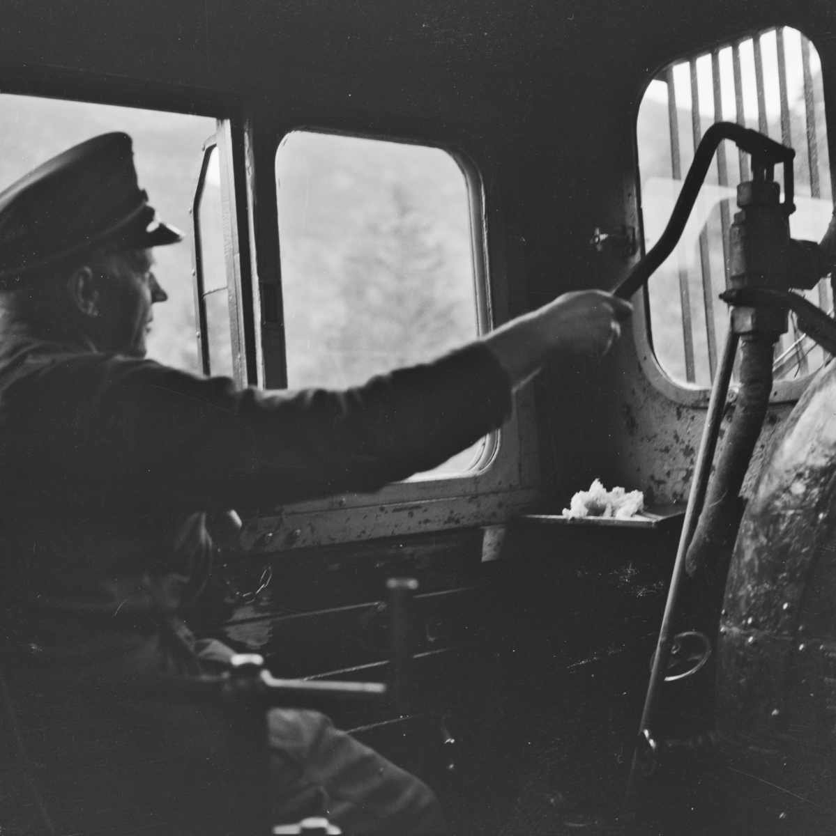 Fyrbøteren på sin arbeidsplass omdord i damplokomotiv 21e 207 på på Numedalsbanen.