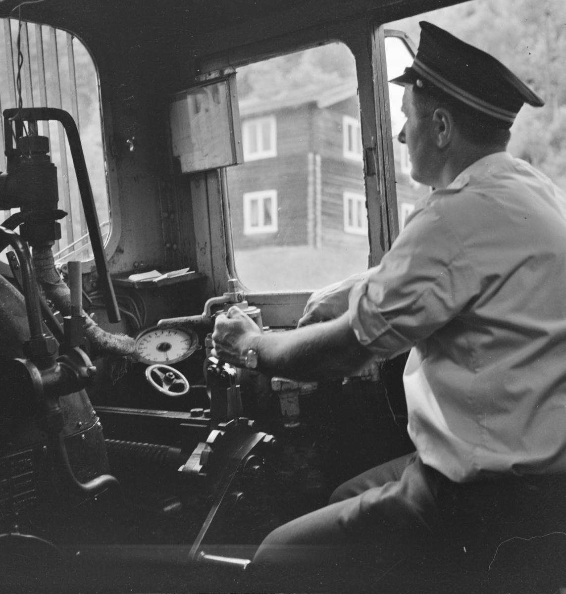 Lokomotivføreren på sin arbeidsplass omdord i damplokomotiv 21e 207 på på Numedalsbanen.