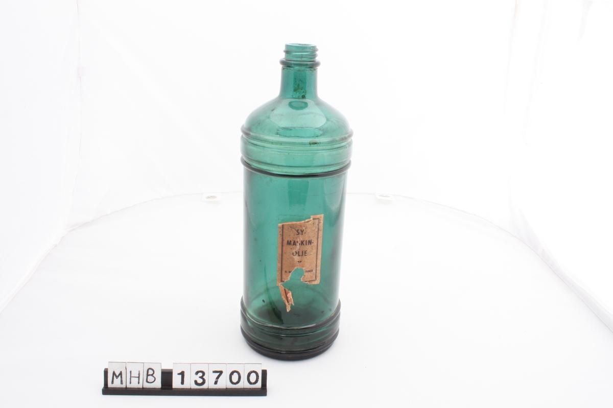 Flaske uten kork, med sirkulær form som. Oppe skråner flasken brått inn mot en smal, kort hals. Både oppe og nede på flasken er et parti med uthevede riller. Midt på flasken er en liten, rektangulær etikett.