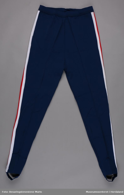 Blå treningsbukse i polyamid, str. 54/56. Strikk under foten, raud og kvit stripe langs sidene.