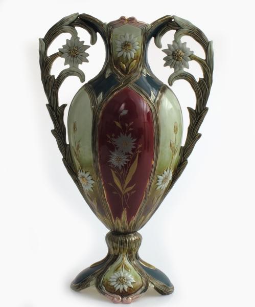 3 praktvaser i sett.   Fajanse  glassur i vinrødt, dypgrønt, gulgrønt, og gull,, hvitt og litt rosa. a-b)  To høye vaser med to hanker formet som bladgren  med hvit blomst. Midtfeltet vinrødt med gul  stilk  med to sølvblomster. Fot av fire bladformer, smal stett, spissbunnet korpus, hals med utbøyd  firefliket munning.   c) oval centerpiece vase med to hanker, på firbladet  fot og stett.