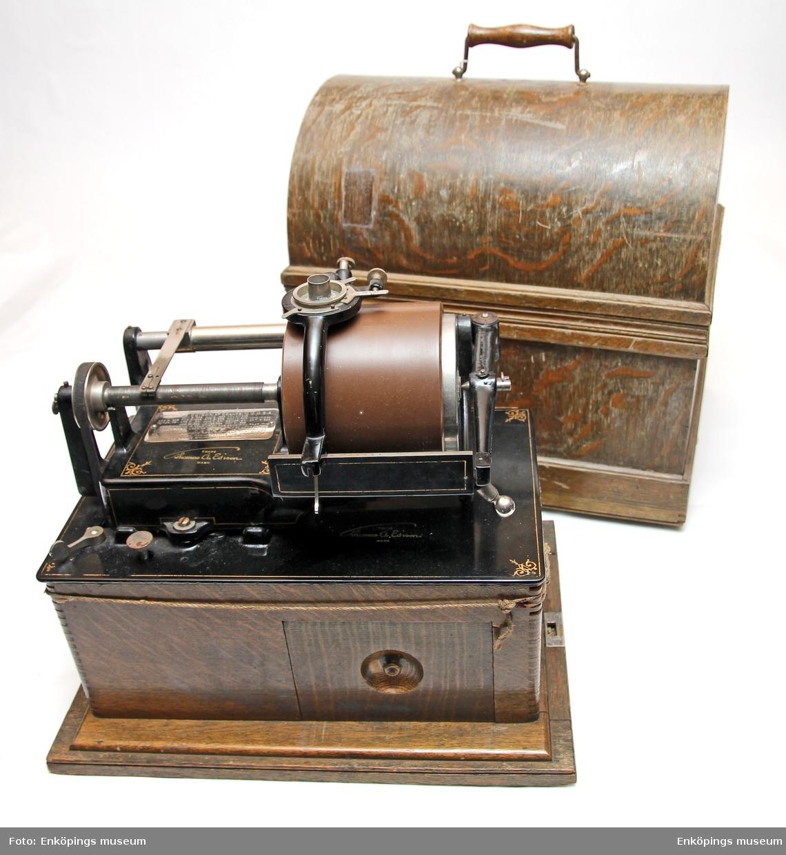 Fonograf inbyggd i trälåda med trähuv (med handtag på). Diverse tillbehör i en liten utdragbar låda på sidan. Svartlackerad, 1 vaxrulle sitter påmonterad. Trähuv som skydd.  Modellnamn C5366