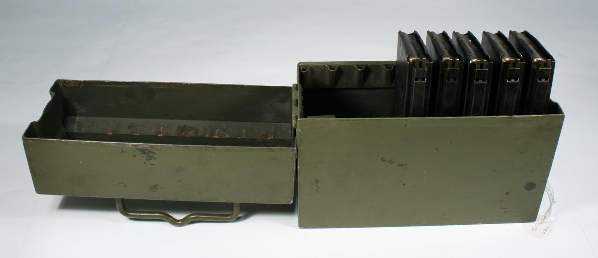 Mørkegrønn magasinboks i metall med plass til 8 magasin. Det er 5 magasin i boksen.
