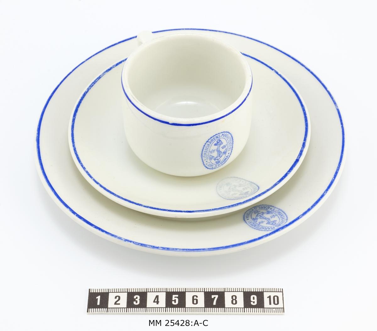Vit kaffekopp med öra. Blå rand runt om vid koppens öppning. På motsatt sida från örat stämpel Sjömanskårens märke. I botten tillverkningsstämpel från Karlskrona porslinsfabrik.