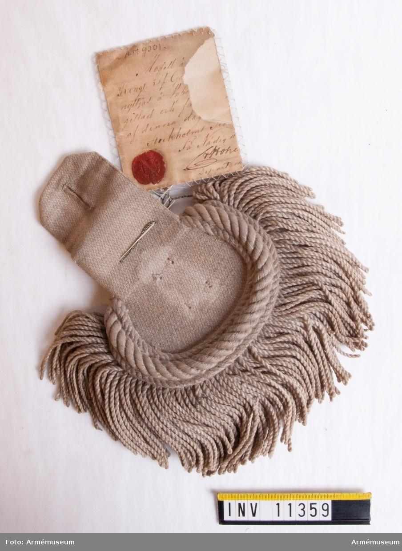 """Grupp C I. Epålett m/1853 av redgarn.  Vidhängande halv modelletikett med text: """"Modell å... Kongl. Lif Ga... nyttjad å Vape... gillad och fa... af denna dag... Stockholms Slo... På Nådigst... (oläslig underskrift) Departem...""""."""