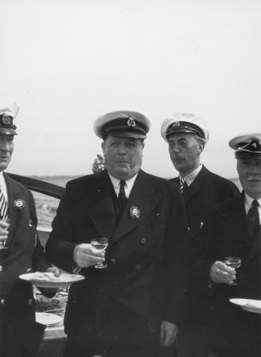 Fyra herrar från Göteborgs Kungliga Segel Sällskap: längst t v Fritz Schéel, i mitten oidentifierad person, näst längst t h Gunnar Carlsson samt i h kanten Birger Jonsson. Att bilden tagits 1935, som anteckningen på baksidan gör gällande, har inte kunnat bekräftas.