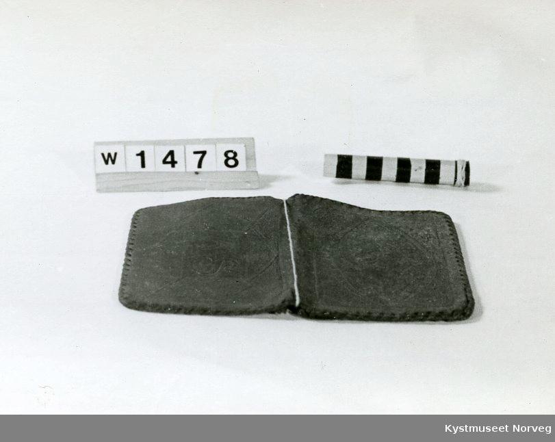 Form: Rektangulær.Lommeboken er sydd rundt kanten med lærreim. Den er inndelt i 5 innvendige rom.