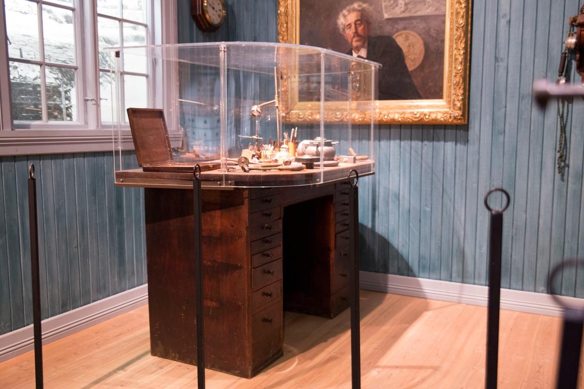 Bordplate med to rette og to avrunede hjørner, plassert på to skufferekker med ti skuffer i hver.