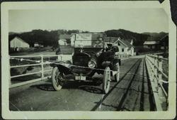 Bil (Ford T) kjørende over en bro, bak rattet en ung dame, v