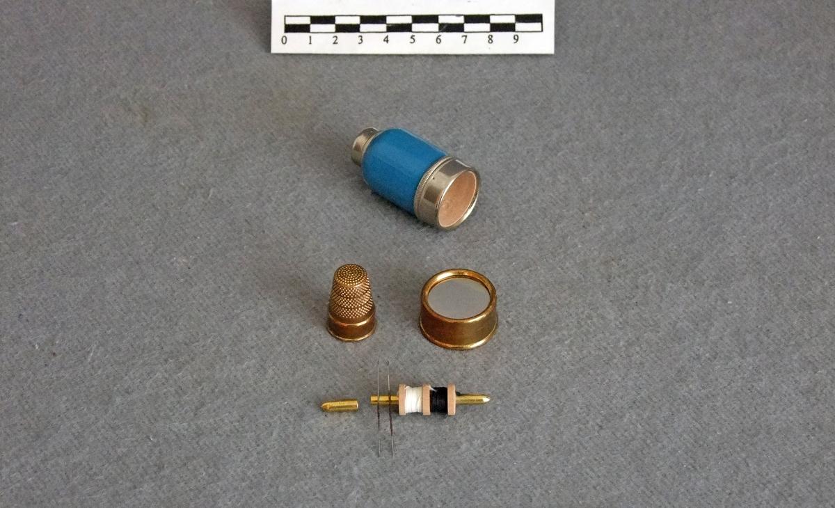 Reisesysett som består av flg. deler:  - to nåler  - en dobbeltsnelle med sort og hvit tråd  - et fingerbøl  - et lite, sirkulært speil.