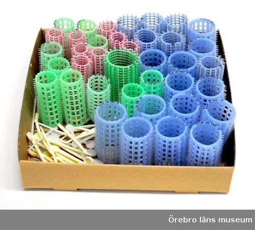 """Papiljotter med tillhörande pinnar av plast. Papiljotterna har taggar utåt som sitter i rader utefter papiljotten. Papiljotterna är av olika storlek och färg:1 st. grön. 13 stycken blåa, 3,5 cm i diameter, 6,4 cm höga, 8 st rosa 2,1 cm i diameter, 6,6 cm höga, 6 stycken blåa 3 cm i diameter, 7,1 cm höga, 10 stycken gröna, 2,7 cm i diameter, 6,2 cm höga.Till papiljotterna finns 36 stycken pinnar av plast. Pinnarna har en rund platta i ena änden, """"huvud"""" och är spetsigt i den andra änden. 22 stycken är gulvita, 14 stycken är vita. Neg.nr.561/91.Gåva av Gunilla Ljungdahl, DyltabrukAnmärkning/värde/placering: Gåva av Gunilla Ljungdahl, Åbytorp, Dyltabruk"""