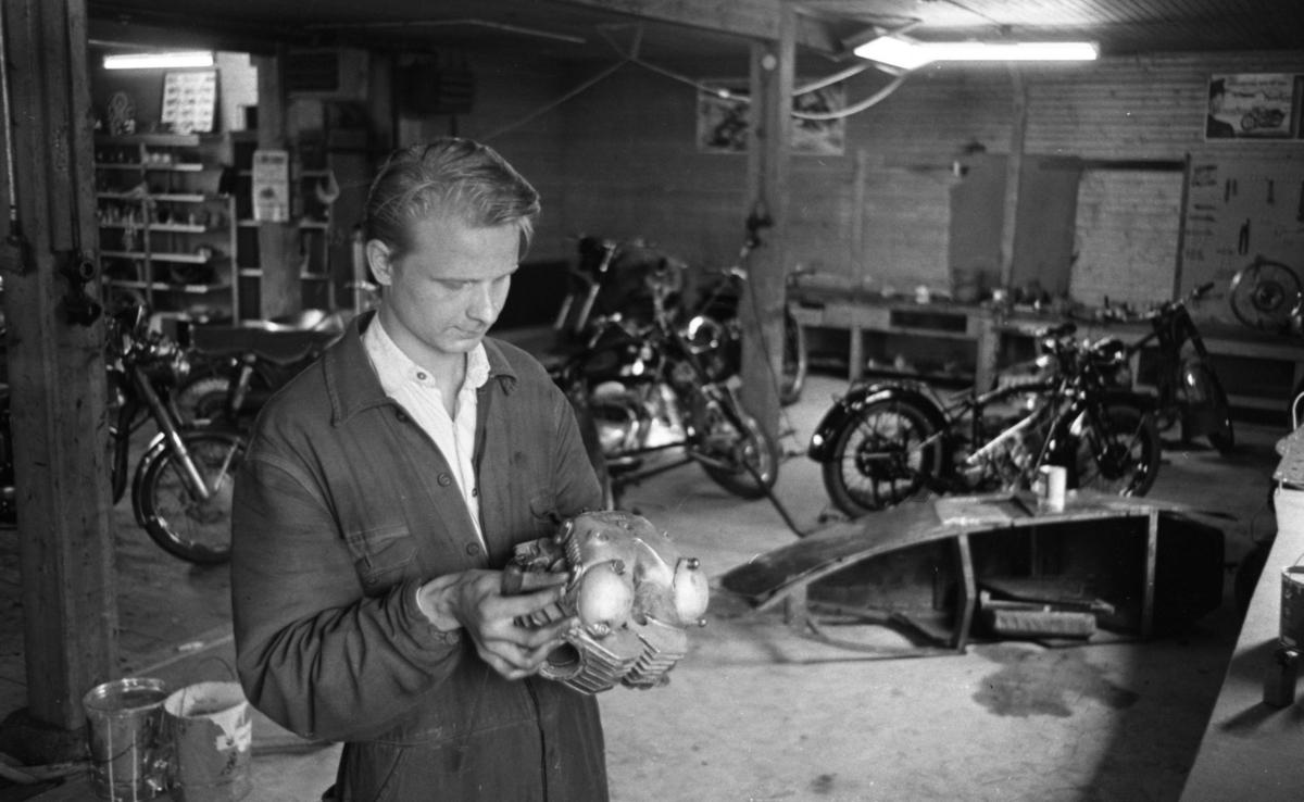 Motorcyklar, långtradare i diket 30 juni 1966En ung man i arbetskläder håller en motor till en motorcykel i sina händer. Motorcyklar syns i bakgrunden.