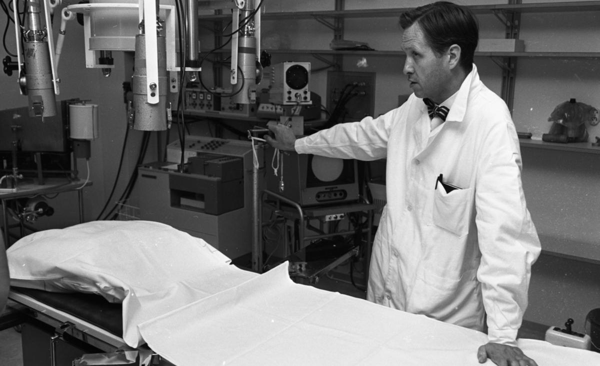 Lasarettet 14 juni 1967En läkare klädd i vit läkarrock, vit skjorta och randig fluga står invid en operationssäng och håller sin vänstra hand på sängen och sin högra hand på undersökningsutrustning som står i bakgrunden.