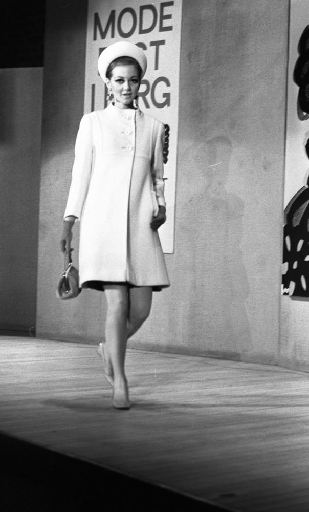 """Modevisning, Görtz motor (Rep av oil) 6 april 1967En fotomodell går på scenen under en modevisning. Hon är klädd i en vit kappa, vit hatt, örhängen, pumps på fötterna, handskar och hon håller en handväska i höger hand. Bakom henne på väggen hänger en skylt med texten: """"Modefest i färg varuhuset Domus."""""""