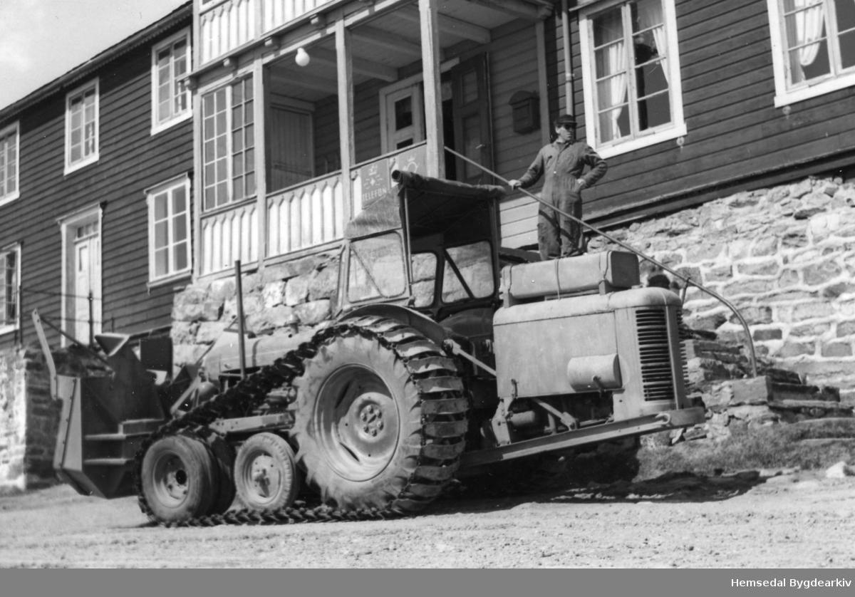 """Fordson Major med heilbelte og Øveråsenfres med eigen motor på Bjøberg i Hemsedal i 1957. Dette var den fyrste skikkelege snøfresaren som vart brukt på Hemsedalsfjellet. Fresaren kunne """"klatra"""" i fennene, og ta dei lag for lag. Jæger Dokk på trappa."""