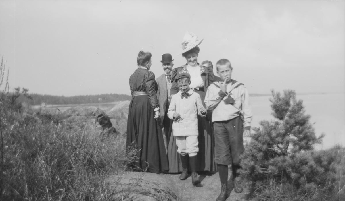 En gruppe bestående av to damer og to menn samt to gutter.  Damen ytterst til høyre er Elise Mathiesen, mannen bak den andre damen er trolig Christian Pierre Mathiesen, og barna i forgrunnen er to av sønnene hans. De står på et sted med utsikt over sjøen.
