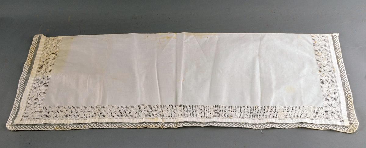 Rektangulært stykke bomullslerret med ein bord i dobbel utrekkssøm langs to kortsider og ei langside, med motiv av åttebladroser. Ei tyllblonde langs tre sider.