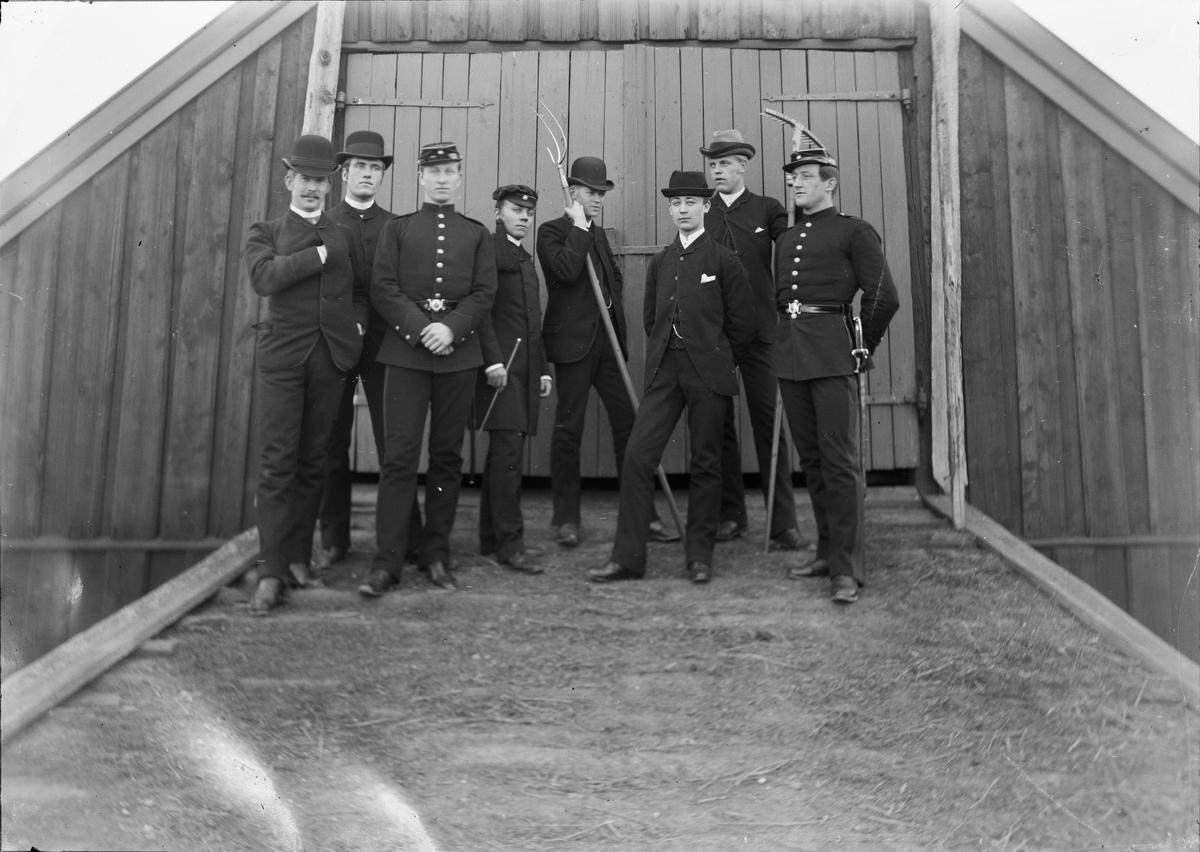 Åtte menn kledd i dress eller uniform står øverst på låvebrua på Linderud Gård. To av guttene i dress holder i ulike jordbruksredskaper, den ene et grip den andre en rake. En av guttene har studenterlue, det er Christian Pierre Mathiesen, to til høyre for ham står Johan Wetlesen..