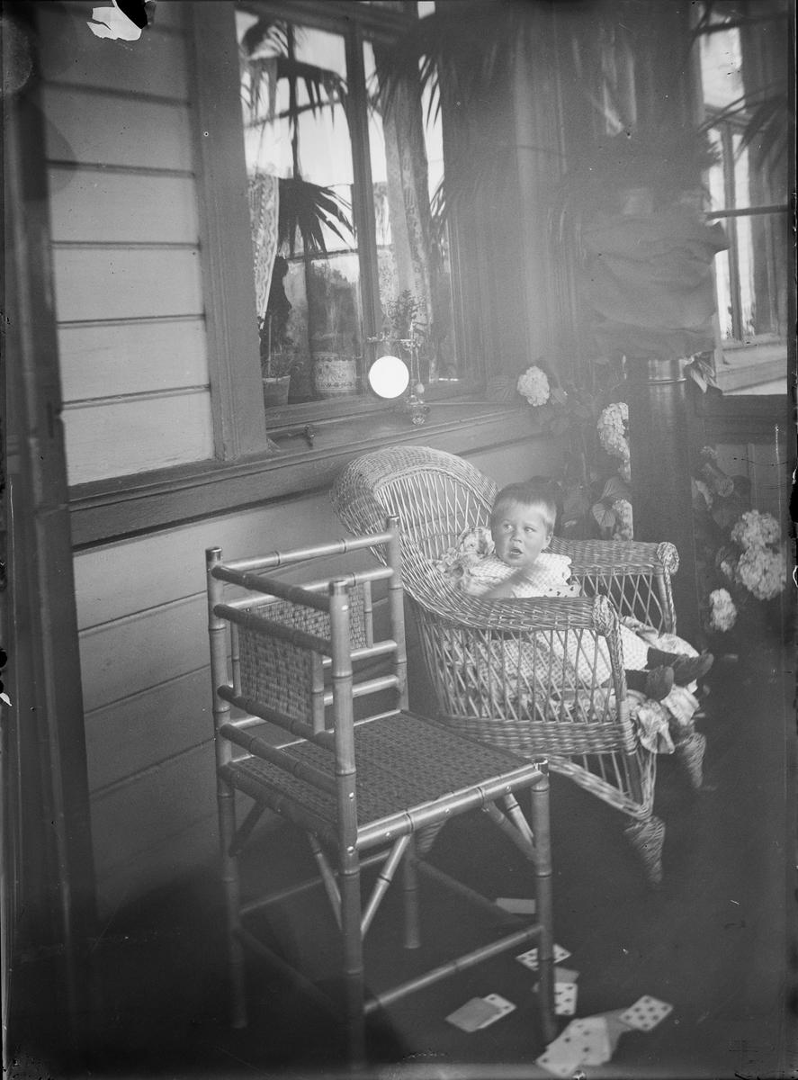 En gutt sitter i en kurvstol på en veranda. På bakken ligger en kortstokk.