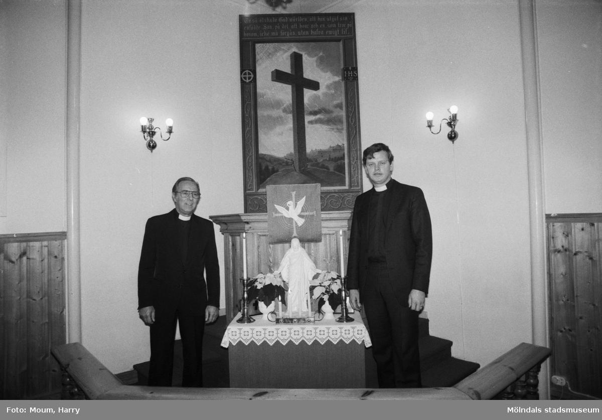"""Greggered kapell i Lindome, år 1983. """"Pastorerna Gustaf Carlstedt och Anders Svensson framför kapellets altartavla.""""  För mer information om bilden se under tilläggsinformation."""